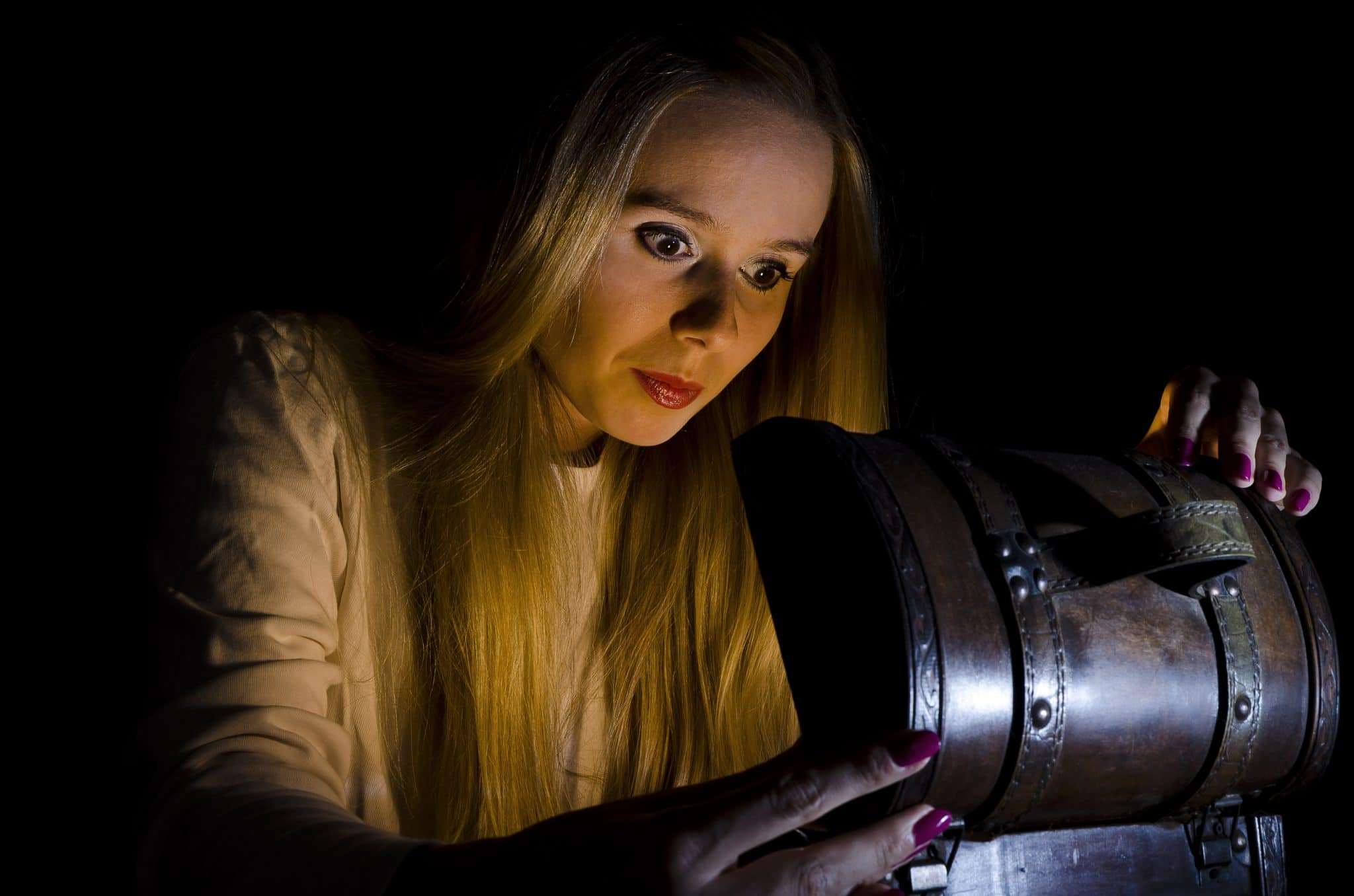 woman opening a small treasure chest in the dark